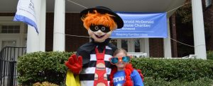 McDonalds mascot character in costume posing with child in funny sunglasses