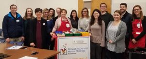 Red Shoe Crew gathered with happy wheels cart and volunteer